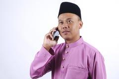 L'homme dans l'habillement traditionnel, se tenant célèbrent Eid Fitr Photos libres de droits