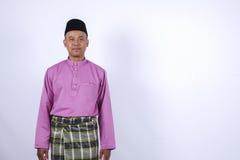L'homme dans l'habillement traditionnel, se tenant célèbrent Eid Fitr Photographie stock libre de droits