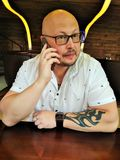 L'homme dans la chemise blanche chauve avec des verres avec un tatouage sur sa main se reposant au bureau et parlant au téléphone Image stock