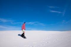 L'homme dans la chemise colorée glisse vers le bas sur un surf des neiges sur le créancier de sable Photographie stock libre de droits