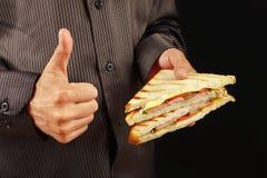 L'homme dans la chemise noire recommande et aime le sandwich sur la fin noire de fond  images stock