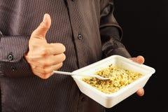 L'homme dans la chemise noire recommande et aime les nouilles instantanées sur le fond noir photos libres de droits