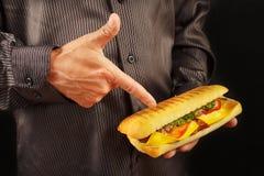 L'homme dans la chemise noire recommande le cheeseburger sur la fin noire de fond  photographie stock