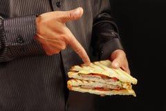 L'homme dans la chemise noire recommande le sandwich sur la fin noire de fond  photos stock