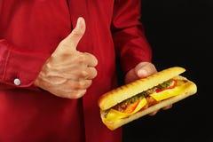 L'homme dans la chemise rouge recommande et aime le grand cheeseburger sur le fond noir images libres de droits