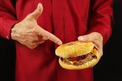 L'homme dans la chemise rouge recommande l'hamburger sur la fin noire de fond  photo libre de droits