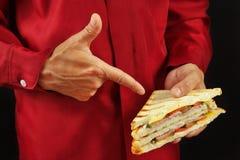 L'homme dans la chemise rouge recommande le double sandwich sur la fin noire de fond  photos stock