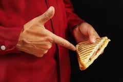 L'homme dans la chemise rouge recommande le sandwich sur la fin noire de fond  photo libre de droits