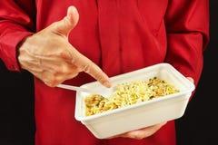 L'homme dans la chemise rouge recommande les nouilles instantanées sur la fin noire de fond  photo stock