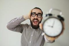 L'homme dans la panique tient le réveil et la tête dans la crainte de la date-butoir photographie stock libre de droits