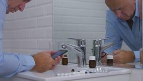 L'homme dans la salle de bains près de quelques pilules de médecine vérifient la boîte d'email de téléphone portable images stock
