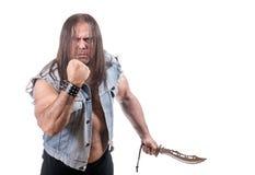 L'homme dans la veste de jeans menacent par le poing et le couteau photographie stock libre de droits