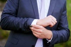 L'homme dans la veste noire utilise des manchettes en parc Photo libre de droits