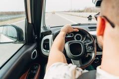 L'homme dans la voiture voyageant sur la route image stock