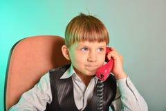 L'homme dans le bureau convient sur les sujets par le téléphone de fil, le concept des affaires des enfants modernes photos libres de droits