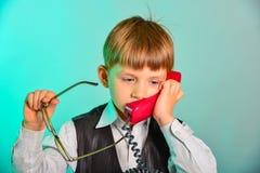 L'homme dans le bureau convient sur les sujets par le téléphone de fil, le concept des affaires des enfants modernes photos stock