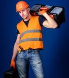 L'homme dans le casque, casque antichoc tient la boîte à outils et la valise avec des outils, fond bleu Travailleur, réparateur,  Image stock