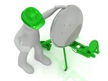 L'homme dans le casque vert ajuste le satellite vert Photos libres de droits