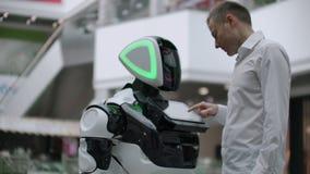 L'homme dans le centre commercial communiquer avec un conseiller de robot Vendeur moderne de magasin et de robot Le robot aide un clips vidéos