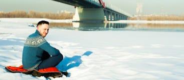 L'homme dans le chandail chaud avec une barbe marche sur la rue pendant l'hiver dans un jour ensoleillé chaud à la rivière images stock