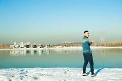 L'homme dans le chandail chaud avec une barbe marche sur la rue pendant l'hiver dans un jour ensoleillé chaud à la rivière image libre de droits
