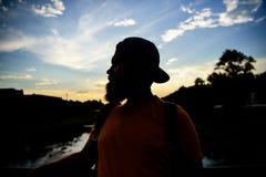 L'homme dans le chapeau apprécient le coucher du soleil tandis que support sur le pont Appréciez le moment agréable Le type devan images libres de droits