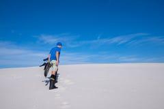 L'homme dans le chapeau bleu avec un surf des neiges monte la dune de sable Image stock