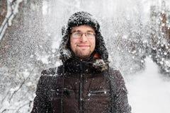 L'homme dans le chapeau d'hiver de fourrure avec l'oreille agite le sourire Photos stock