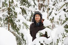 L'homme dans le chapeau d'hiver de fourrure avec l'oreille agite le portrait de sourire photo libre de droits