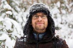 L'homme dans le chapeau d'hiver de fourrure avec l'oreille agite le portrait de sourire photos stock