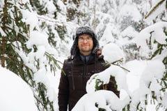 L'homme dans le chapeau d'hiver de fourrure avec l'oreille agite le portrait de sourire images stock