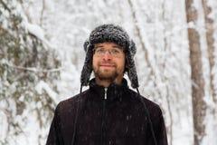 L'homme dans le chapeau d'hiver de fourrure avec l'oreille agite le portrait de sourire photos libres de droits