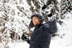 L'homme dans le chapeau d'hiver de fourrure avec l'oreille agite le portrait de sourire image stock