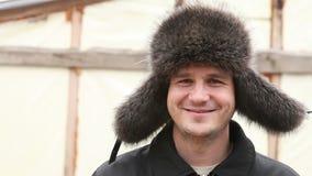 L'homme dans le chapeau de fourrure d'hiver regarde dans l'appareil-photo banque de vidéos
