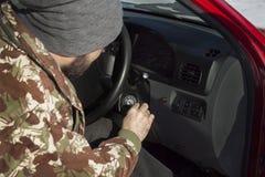 L'homme dans le chapeau met les clés dans l'allumage de la voiture Images libres de droits