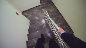 L'homme dans le costume descend la vue de marbre d'escaliers du headcam banque de vidéos