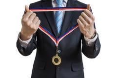 L'homme dans le costume donne la médaille D'isolement sur le fond blanc Photos libres de droits