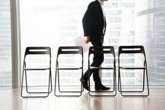 L'homme dans le costume marche après des chaises dans la rangée Photographie stock libre de droits