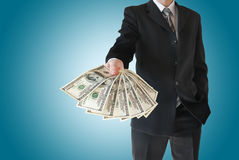 L'homme dans le costume noir offre l'argent d'isolement sur le fond bleu Photographie stock