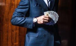 L'homme dans le costume pose avec des cartes sur le fond en bois photographie stock
