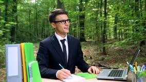 L'homme dans le costume se reposant au bureau en parc ensoleillé, écrivant commencent vers le haut des idées, inspiration images stock