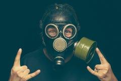 L'homme dans le masque de gaz avec les yeux fous faisant la roche signent par les deux mains Image stock