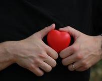 L'homme dans le T-shirt noir tient le coeur rouge dans des paumes Photos libres de droits