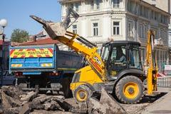 L'homme dans le tracteur jaune enlève le vieux trottoir d'asphalte Images stock