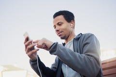 L'homme dans les sports uniforme et écouteurs écoute la musique utilisant un smartphone Photos libres de droits