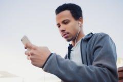 L'homme dans les sports uniforme et écouteurs écoute la musique utilisant un smartphone Photographie stock