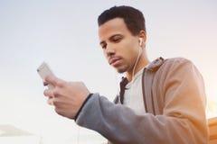 L'homme dans les sports uniforme et écouteurs écoute la musique utilisant un smartphone Images libres de droits