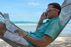 L'homme dans les tropiques et avec les jeunes d'ordinateur la beauté se situant dans un hamac avec l'ordinateur portable dans le  Photographie stock