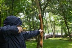 l'homme dans un capot, les tractions une ficelle d'arc et les prises visent un tir à la cible photo stock