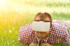 L'homme dans un casque de réalité virtuelle se trouve sur une herbe verte Photographie stock libre de droits